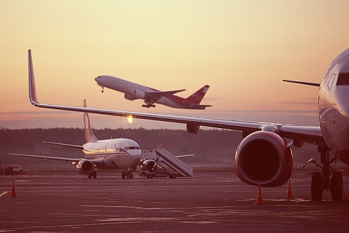 Image of an aircraft taking off into a sunset sky whilst two aircraft remain on the runway.