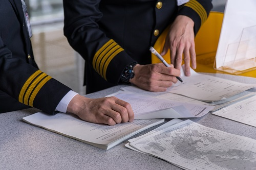 Image shows two airline pilots reading paper based flight documents and making notes before departure.