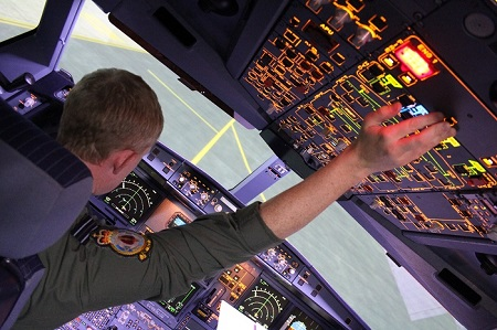 Air Tanker pilot in the cockpit of an aircraft reaching overhead to flick a switch during the pre-flight check.