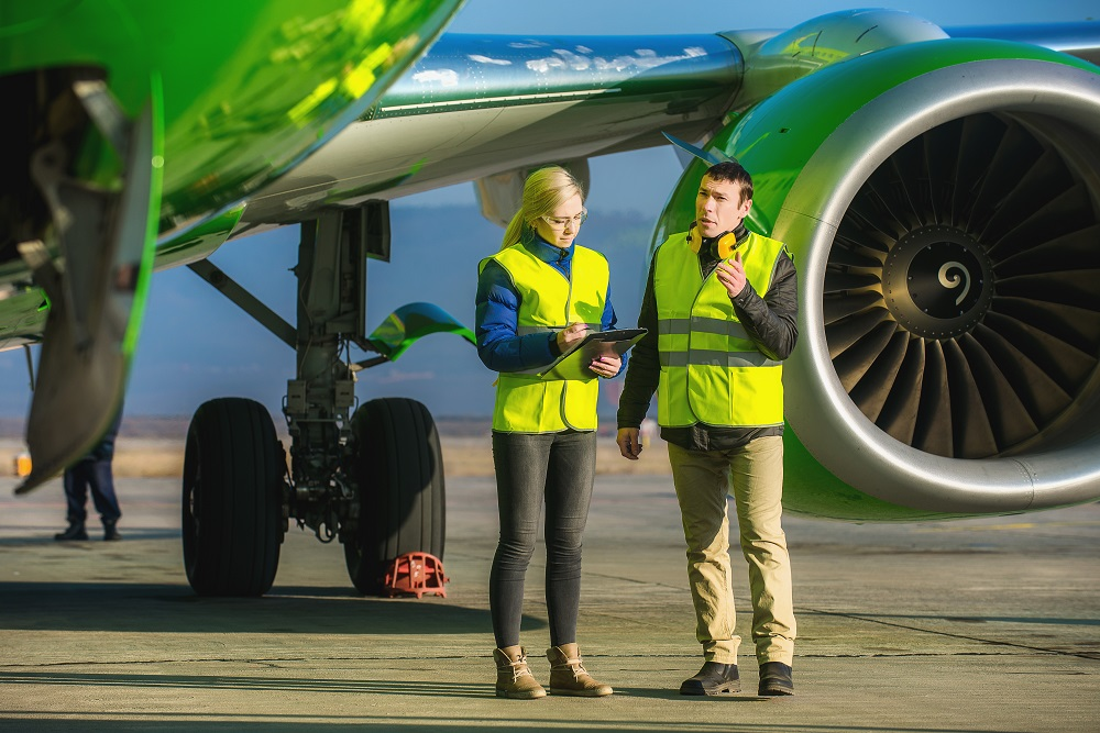 Ground crew stand in front of a jet engine as they inspect an airplane as it stands on the runway. She's looking at a clipboard as he is talking to her
