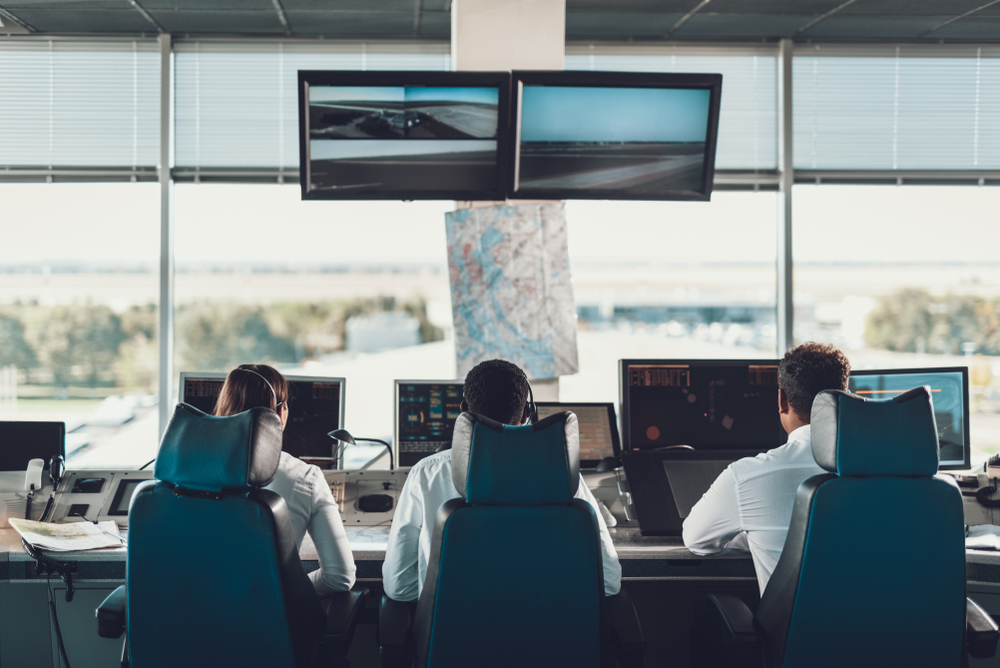 A female and two male flight dispatchers are sat in front of monitors tracking flights and weather conditions.