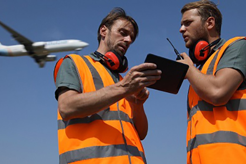 Two male flight dispatchers using the Electronic Flight Bag app on a device as an airplane takes off overhead.