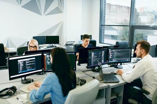 Software Developers sat at desks in an office working on their computer screens. There are two female and two male developers sat opposite one another.