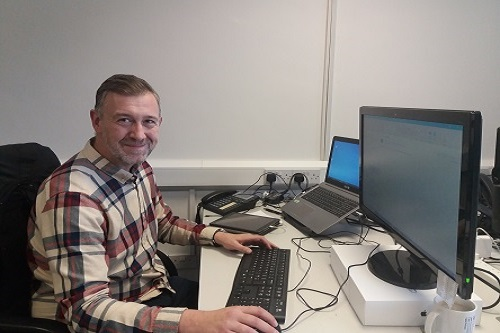 Pictured is Ross Aitkin, IT Support Manager, sat at his desk smiling to the camera. On his desk is a laptop and separate screen, keyboard and mouse.