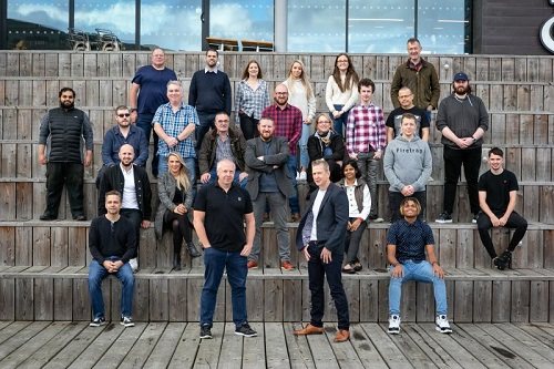 This is an image of the Bytron team pictured at The Deep in Hull. The managers are at the forefront of the image and the rest of the team are stood or sitting behind them.
